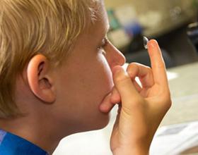 Мальчик надевает линзы